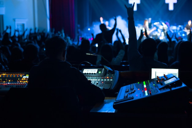 Soundman working on the mixing console in concert hall