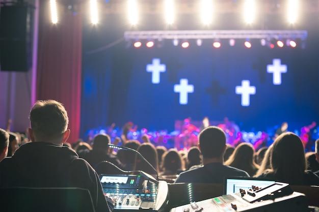 Звукорежиссер работает на микшерном пульте в концертном зале