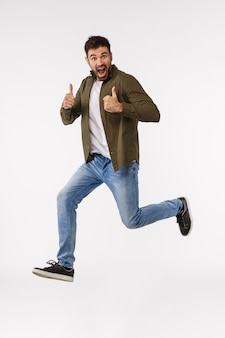 Sounds nice. full-length vertical studio shot cheerful triumphing caucasian bearded man in street outfit, jumping from amazement and rejoice, winning, become champion, celebrating great news