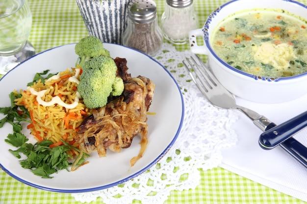 Суп и рис с мясом в тарелках на салфетке на скатерти