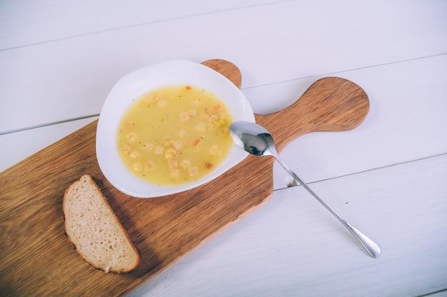 木製のテーブルの上のパンとボウルのスープスープ。