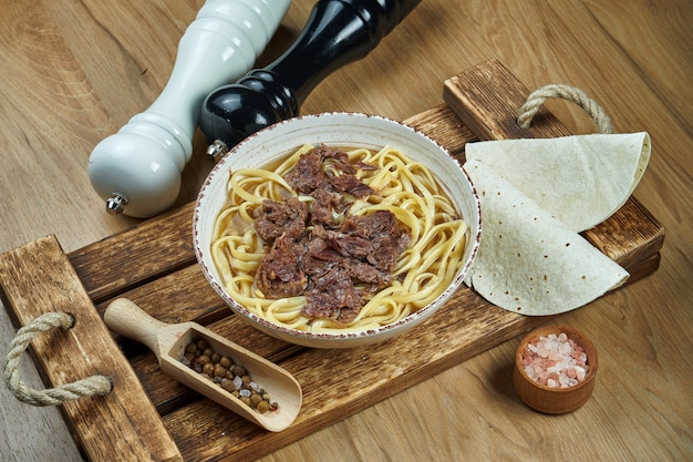 Soup on the broth with noodles and stewed beef in a white ceramic plate on a wooden tray. food flat lay