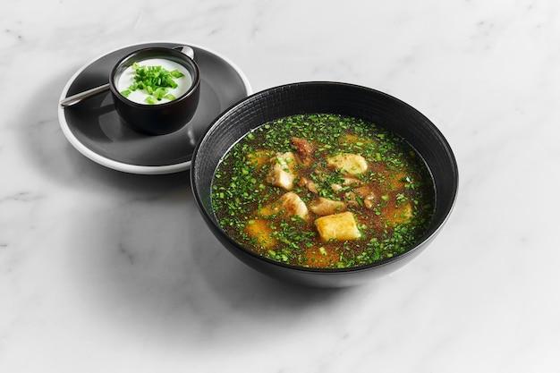 Суп, бульон с белыми грибами со свежей зеленью