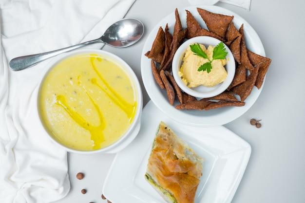 Суп-сыр с брокколи в белой тарелке на белом фоне.