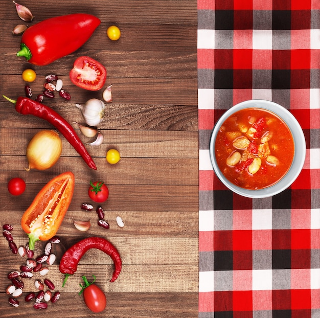 Soup chili con carne on wooden background surrounded by vegetables.
