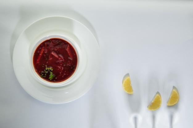 ワイングラスからの影と白い表面にレモンスライスとプレートのスープ