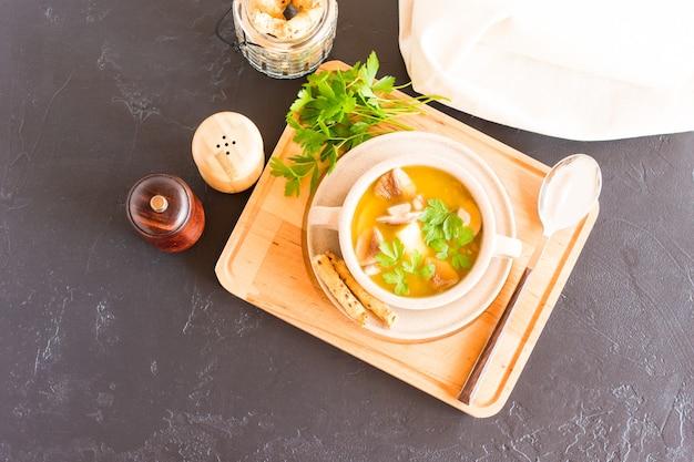 허브와 함께 수프 그릇에 신선한 흰색 버섯 수프. 나무 스탠드에. 평면도.