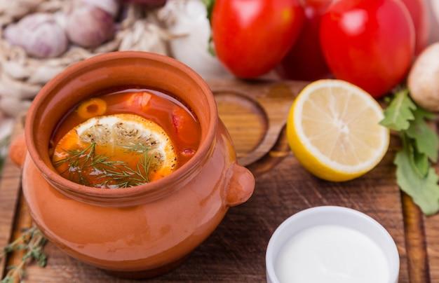 Суп из солянки с гарниром в коричневой керамической кастрюле
