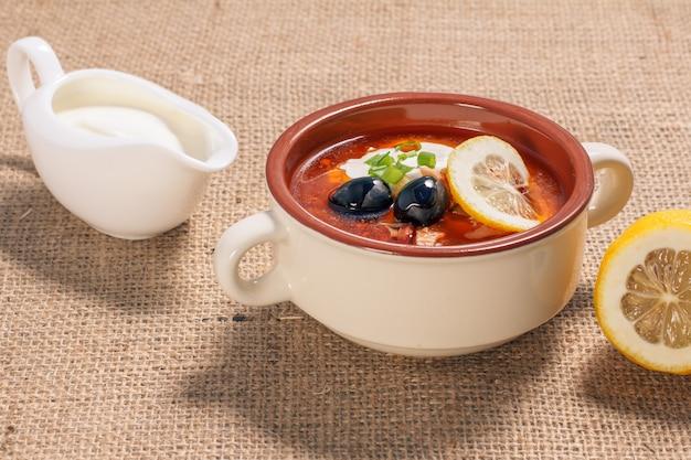 肉、スモークソーセージ、ジャガイモ、トマト、きゅうりのピクルスのマリネ、レモン、ブラックオリーブ、サワークリームを荒布の上に白いセラミックスープボウルに入れたスープソルトワート