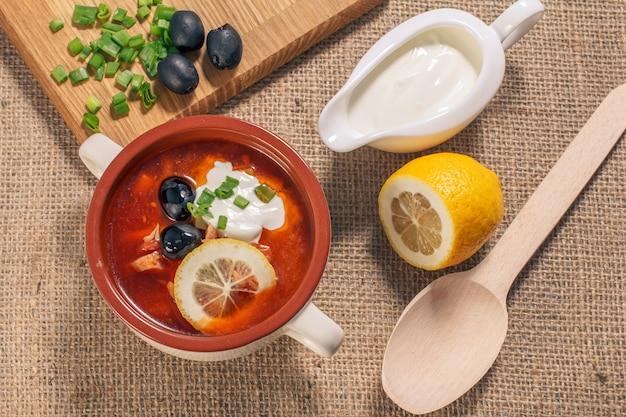 肉、スモークソーセージ、ジャガイモ、トマト、きゅうりのピクルス、レモン、ブラックオリーブ、サワークリームをまな板と木のスプーンで白いセラミックスープボウルに入れたスープソルトワート