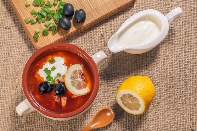 まな板付きの白いセラミックスープボウルに肉、スモークソーセージ、ジャガイモ、トマト、きゅうりのピクルス、レモン、ブラックオリーブ、サワークリームを添えたスープソルトワート