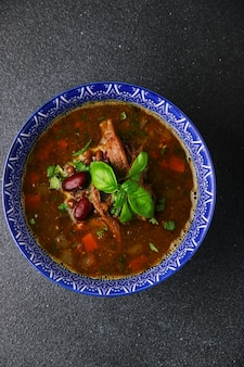 Soup with beans and meat in bowl on dark table closeup.