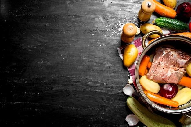 검은 나무 테이블에 쇠고기와 다양한 야채 수프