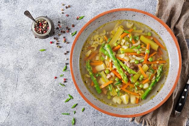 牛肉、アスパラガス、グリーンピース、ニンジン、セロリが入ったスープ。上面図。