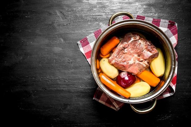검은 나무 테이블에 냄비에 쇠고기, 당근, 신선한 감자와 수프.