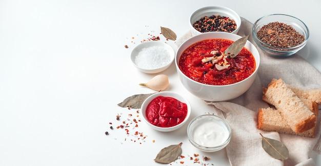 빵과 베이 잎의 배경에 사탕 무 우, 마늘, 사 우 어 크림 수프, 밝은 배경에 보르시. 측면에서 물, 파노라마.