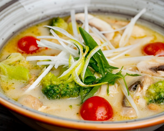 Soup with broccoli tomatoes mushrooms and greens
