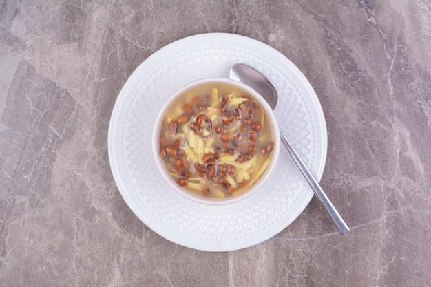 白いセラミックカップに入った茶色の豆とスパゲッティのスープ