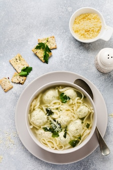 Суп с куриными фрикадельками и яичной пастой, сыром пармезан, петрушкой в керамической миске на серой поверхности стола. традиционный итальянский бульон. вид сверху.