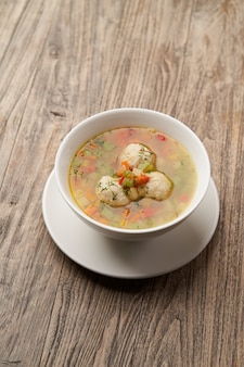 Soup with chicken meatballs and vegetables. white plate with traditional jewish passover dish matzo ball soup