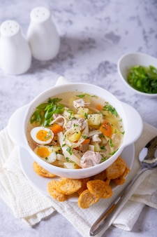 Soup with chicken, noodles, potatoes, quail eggs, and carrots