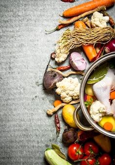Суп с курицей, овощами и специями. на каменном столе.
