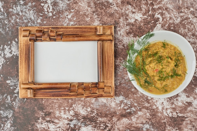 白いカップで提供されるハーブのスープ、上面図。