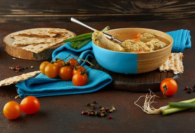 Суп с клецками из мацы и курицей с морковью и помидорами. здоровая пища на пасху.