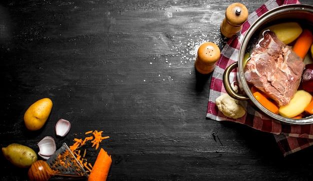 검은 나무 테이블에 고기, 야채, 향신료와 수프.