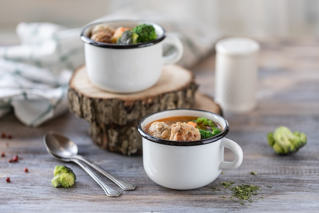 Soup with meatballs in metal mugs on wooden table