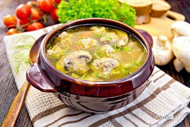 木の板の背景にナプキン、パセリ、トマト、マッシュルーム、パンの粘土ボウルにミートボール、麺、シャンピニオンを入れたスープ