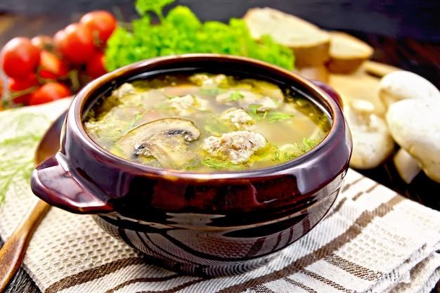 粘土のボウルにミートボール、麺、シャンピニオンのスープ、タオルにスプーン、パセリ、トマト、マッシュルーム、木の板の背景にパン