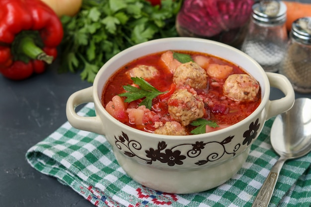 Soup with meatballs and vegetables in a bowl against a dark wall