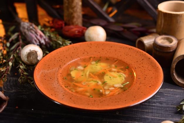 キノコとニンジンのスープ。装飾が施された黒い木製テーブル