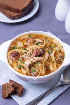 Суп с грибами, курицей и лапшой в белой тарелке. традиционное русское блюдо. крупный план.