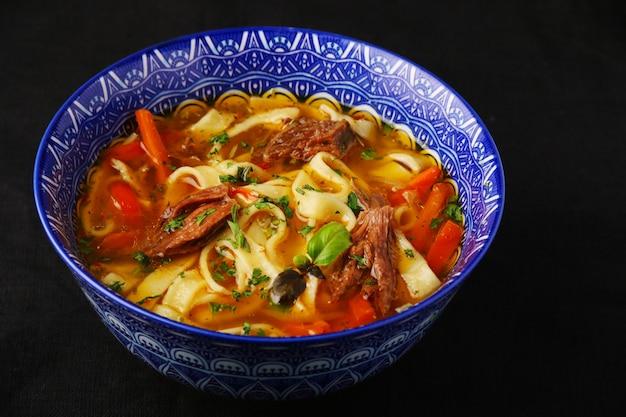Суп с лапшой и крупным планом говядины. лагман. национальное узбекское блюдо.