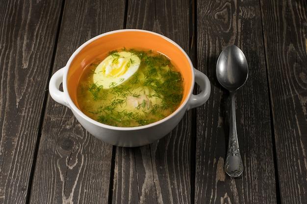 麺、鶏肉、卵、スプーンで皿に暗い背景の木のディルのスープ
