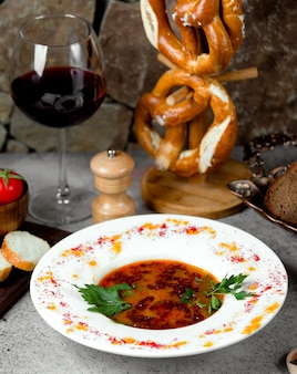 Soup with pomegranate inside and glass of wine