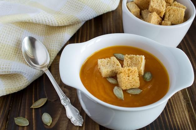 木製の背景にカボチャとラスクのスープ