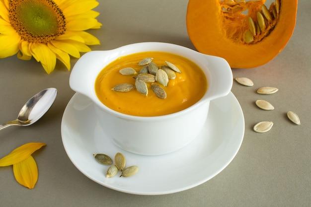 灰色の白いプレートにカボチャのスープ