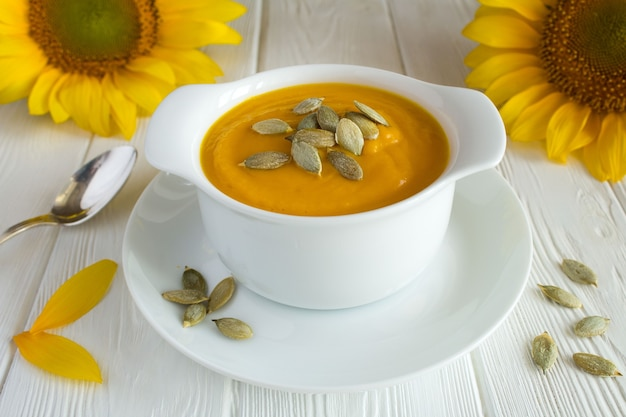 Soup with pumpkin  in the plate on the white wooden