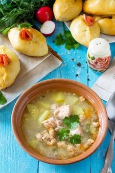 サーモンの耳とキッチンの木製の背景に赤い魚とオープンパイのスープ