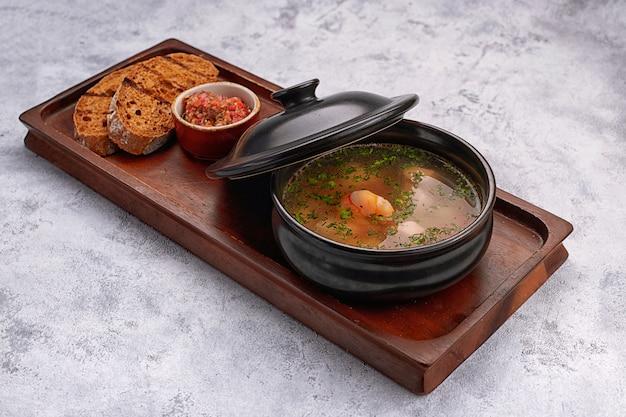 Суп с креветками, соусом из хлебных гренок на деревянной доске на белом фоне