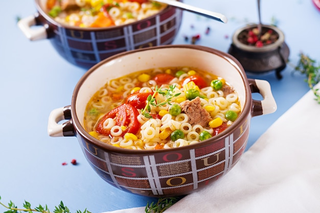 Soup with small pasta, vegetables and pieces of meat in  bowl on  blue table. italian food.