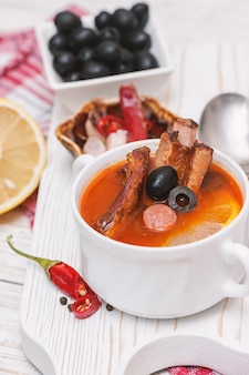 Soup with smoked meat, olives and lemon. solyanka soup