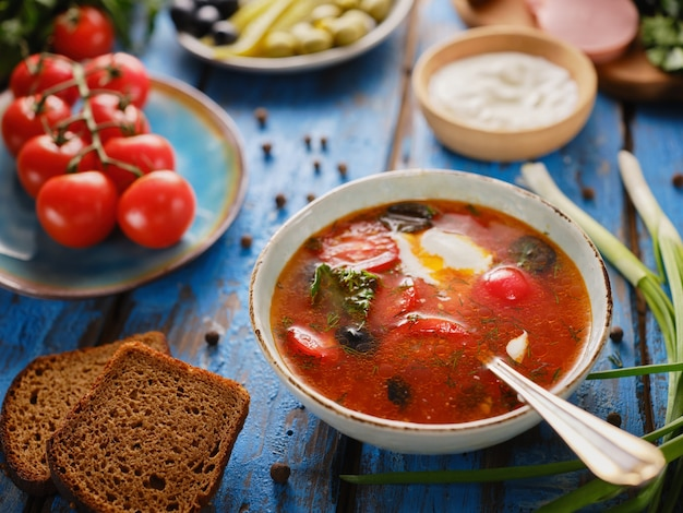 Soup with tomatoes, hodgepodge, borscht on a blue table