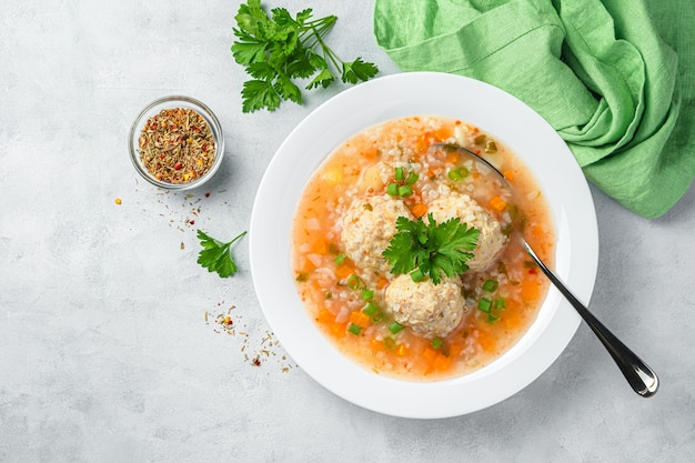 Суп с фрикадельками из мяса индейки и овощами на сером фоне. здоровое, диетическое питание. вид сверху, копия пространства.