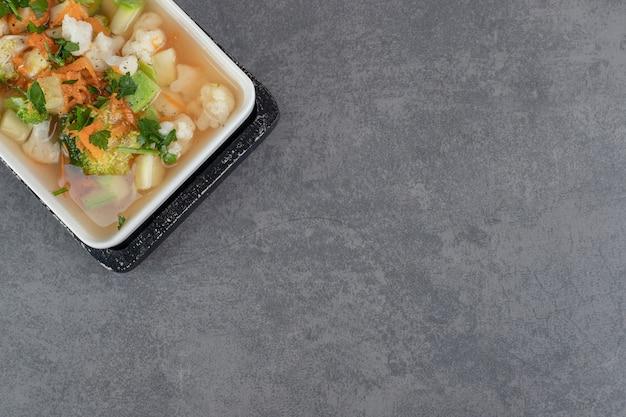 Zuppa con varie fette di verdure sul piatto bianco. foto di alta qualità