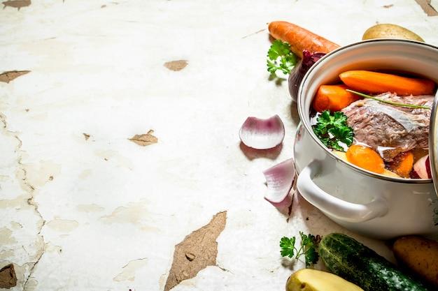 냄비에 야채, 돼지 고기, 향신료, 허브를 넣은 수프.