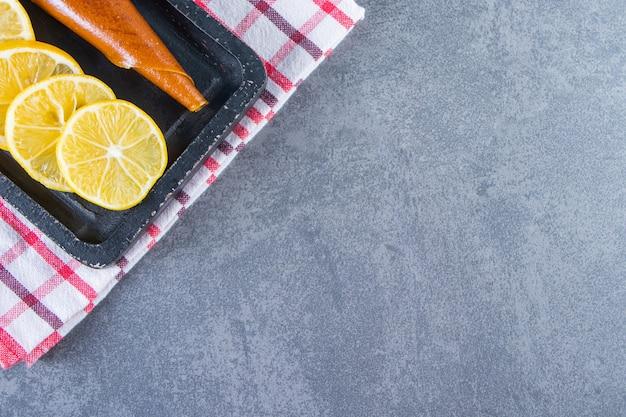 Киснуть и нарезать лимон на доске на кухонном полотенце на мраморной поверхности.